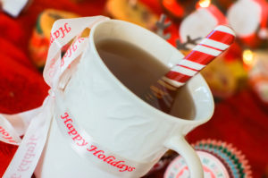 An image of a cup of tea with a ribbon that says 'Happy Holidays'