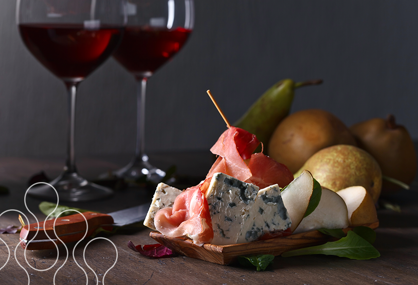 An image of a charcuterie board with two glasses of wine