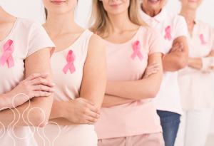 A few women wearing pink breast cancer awareness ribbons standing together