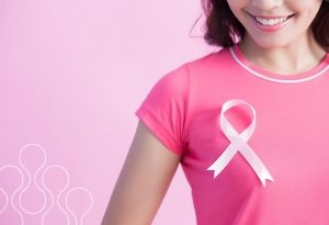 A woman wearing a pink ribbon to represent breast cancer awareness